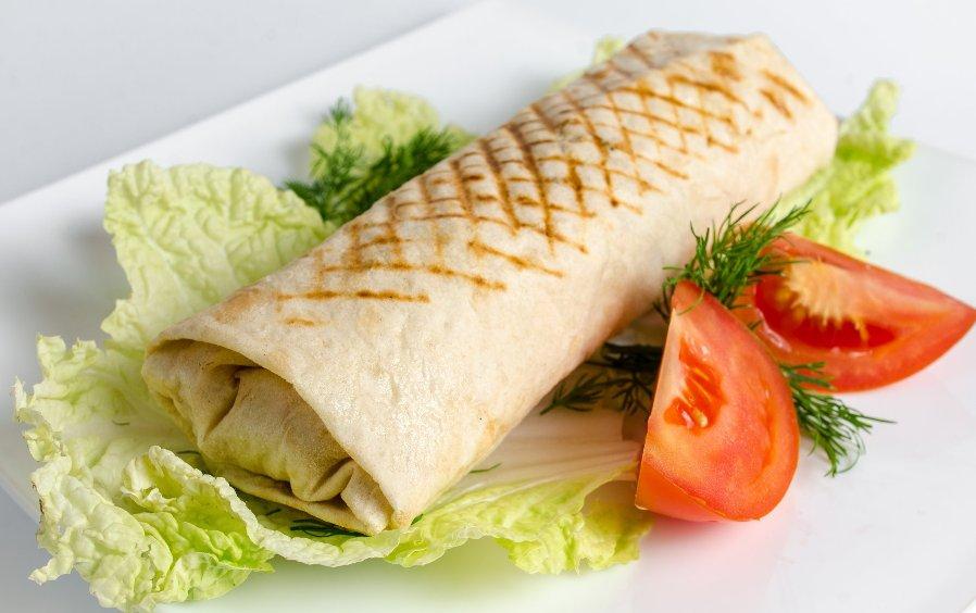 фото недорогой аккуратно завернутой шавермы на листе салата с укропчиком и помидорами