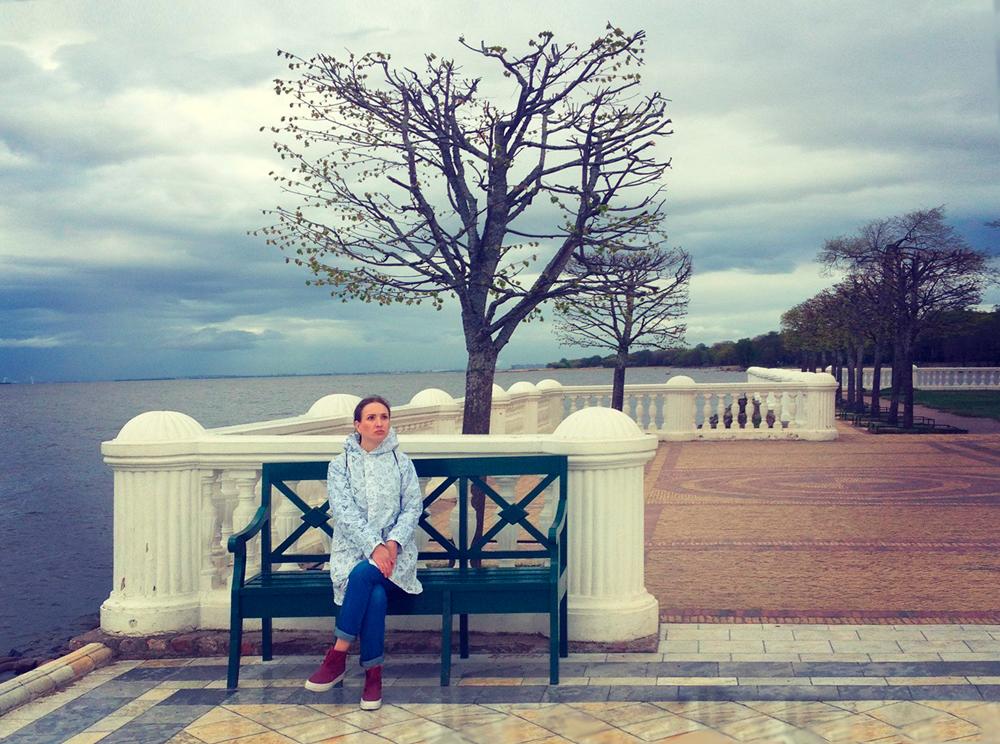 Одинокая, грустная девушка сидит на скамейке возле Финского залива
