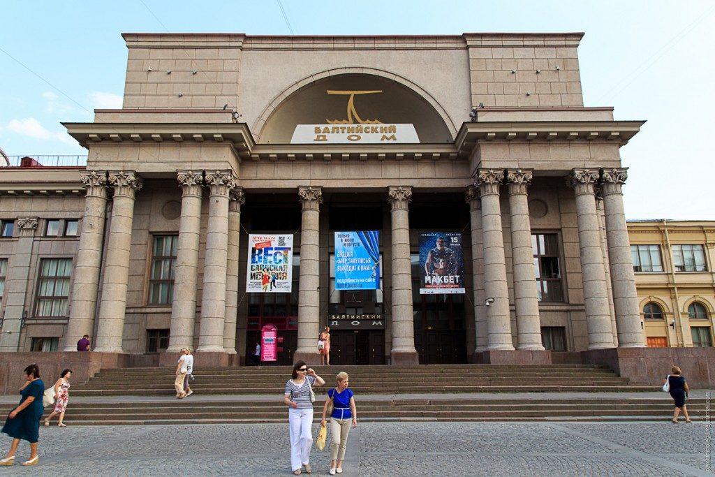 Люди идут пешком возле театра