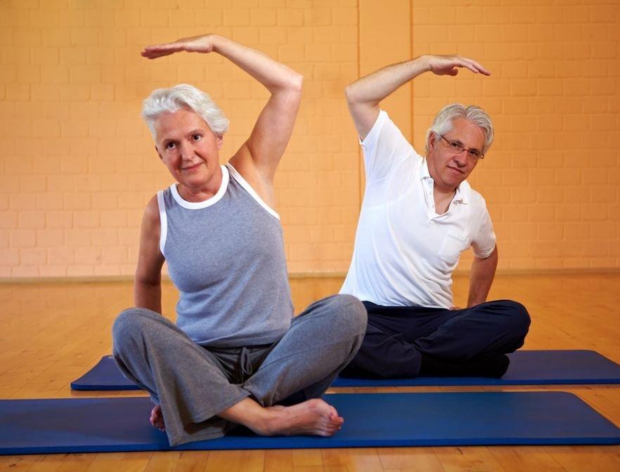 Бабушка и дедушка делают упражнения на коврике