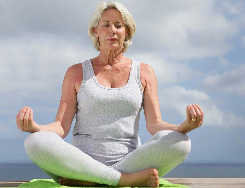 Женщина в возрасте медитирует