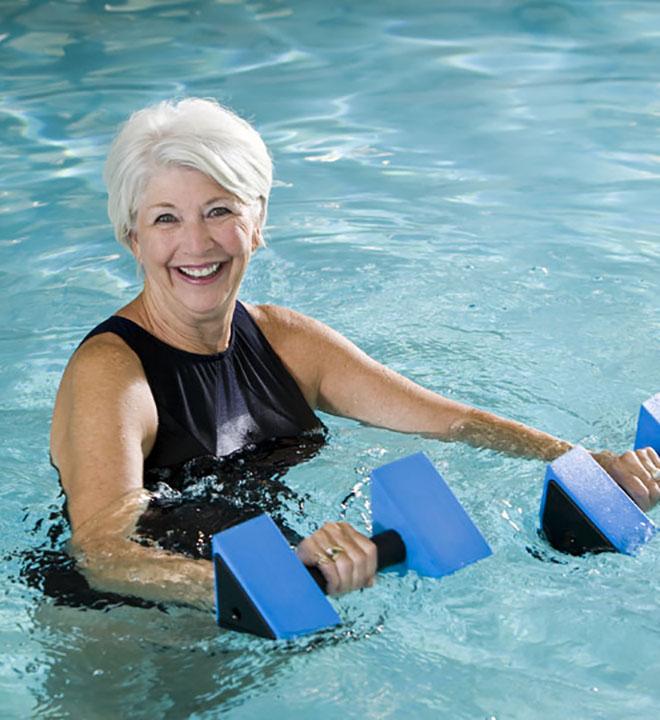 Пожилая женщина купается в бассейне